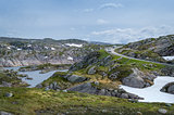 Scenic Norwegian landscape with rocks, lake and curved mountain road.