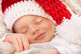 Cute baby Santa smiling in the sleep
