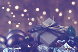 Shabby chic gift nestled in Christmas decorations with bokeh lig
