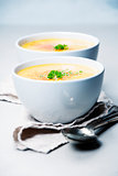 Pumpkin cream soup in bowl over grey concrete background