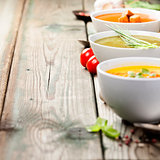 Variety of cream soups over old wood background