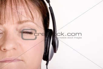 Older female listening to music on headphones