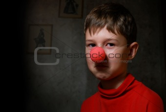 The upset boy with clown's nose in dark room