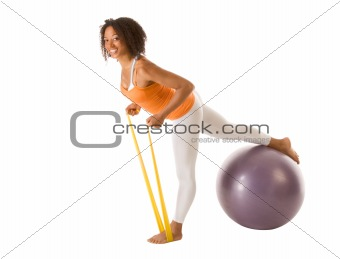 Sporty woman stretching with resistance bands and ball