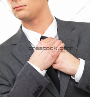 Close up portrait of a business man adjusting tie