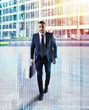 Determinated businessman walking in the city. double exposure
