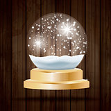 Christmas Crystal Ball with Snow on Wooden Background.