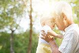Grandfather kissing grandson.