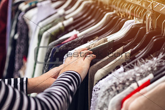 Woman browsing through clothing at second hand street market
