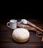 wheat yeast dough in a wooden bowl on a table
