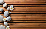 zen pebbles and spa flowers set on hammam wooden board