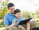 Happy Father and Son Playing on a Computer Tablet Outside.