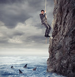 Businessman is likely to fall into the sea with sharks. concept of problems and difficulty in business