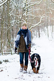 Woman with her dog hiking or walking in winter
