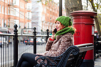 Young London lifestyle woman Talking on Mobile with red postbox
