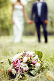 wedding flowers bouquet laying on green grass in park, bride and groom blurred on background holding hands, lifestyle people concept