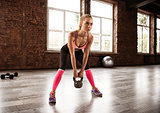 Blonde girl working out at the gym with a kettlebell