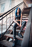 Pretty blue-haired rock girl (informal model), dressed in black leather pants and topic, sits on stairway
