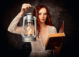 Sexy red-haired young girl with kerosene lamp reading book