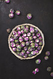 Purple Brussels sprouts in a bowl on dark background