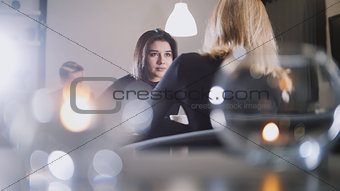 Pretty young woman with black hair drinking coffee and talking with girlfriend in the cafe