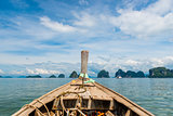 close-up of a Thai wooden boat sailing to beautiful rocks at sea