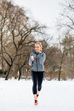 Woman running down a path on winter day in park