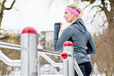 Young woman training her legs on fitness path on winter day