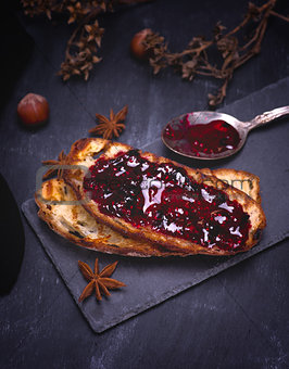toast of white bread with raspberry jam on a black surface