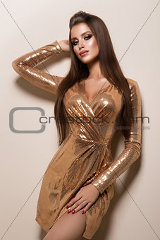 Beautiful woman with professional make up. Gold dress