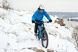 Cyclist in Blue Riding Mountain Bike on Rocky Winter Hill Covered with Snow. Extreme Sport and Enduro Biking Concept.