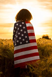 Girl Teenager Woman Wrapped in USA Flag in Field at Sunset
