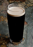 Glass of stout beer top with white foam