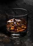 Elegant glass of whiskey with ice cubes on stone