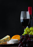 Bottle and glass of red wine with cheese selection