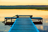 view of a wooden pier near a picturesque calm lake at dawn