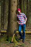 relaxed forester resting with an ax, leaning against a tree