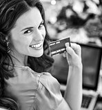Portrait of smiling young woman with credit card using laptop in