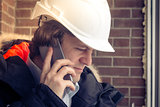 Construction inspector in white helmet talking on mobile phone on the brown brick wall background. Soft focus, toned. Close up.