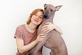 A woman hugging with a Mexican Hairless Dog