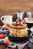 Stack of freshly prepared banana  pancakes with fresh berries