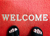 Closeup red mat with welcome and foot