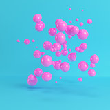 Pink flying spheres on bright blue background in pastel colors