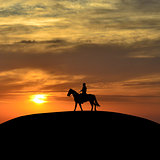 Horseback rider at sunset