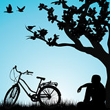 Relaxing bicyclist  under a tree