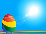 Striped Easter egg on rainbow over blue sky