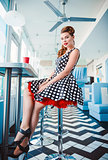 Retro (vintage) portrait of smiling cute young girl sitting in cafe. Pin up style portrait of young girl in dress