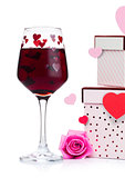 Glass of red wine with heart and pink gift box