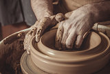 elderly man making pot using pottery wheel in studio