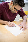 Young Designer Drawing the Sketch Using Pencil on the Wooden Table in Bright Studio